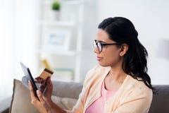有片剂个人计算机和信用卡的愉快的妇女在家 库存图片