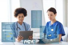 有片剂个人计算机和剪贴板的医生在医院 免版税库存照片