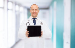 有片剂个人计算机和听诊器的微笑的男性医生 库存照片