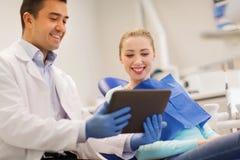 有片剂个人计算机和妇女患者的男性牙医 库存图片