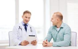有片剂个人计算机和患者的医生在医院 库存照片