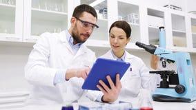 有片剂个人计算机和显微镜的科学家在实验室 股票视频
