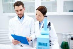 有片剂个人计算机和显微镜的科学家在实验室 免版税库存照片