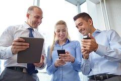 有片剂个人计算机和智能手机的商人 图库摄影