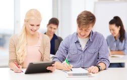 有片剂个人计算机和笔记本的两名微笑的学生 库存照片
