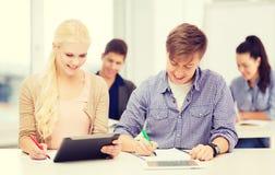 有片剂个人计算机和笔记本的两名微笑的学生 库存图片