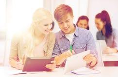 有片剂个人计算机和笔记本的两名微笑的学生 图库摄影
