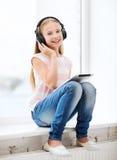 有片剂个人计算机和耳机的女孩在家 库存图片
