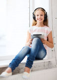 有片剂个人计算机和耳机的女孩在家 免版税库存图片