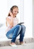 有片剂个人计算机和耳机的女孩在家 免版税库存照片