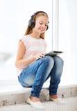 有片剂个人计算机和耳机的女孩在家 库存照片