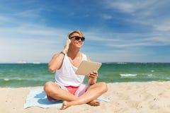 有片剂个人计算机和耳机的愉快的人在海滩 免版税库存照片