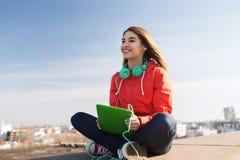 有片剂个人计算机和耳机的愉快的少妇 免版税库存图片