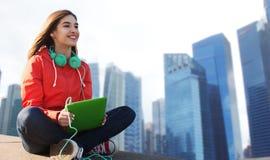 有片剂个人计算机和耳机的愉快的少妇 免版税库存照片
