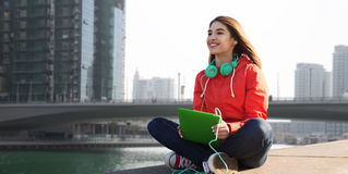 有片剂个人计算机和耳机的愉快的少妇 免版税图库摄影