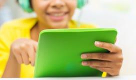 有片剂个人计算机和耳机的愉快的非洲妇女 图库摄影