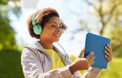 有片剂个人计算机和耳机的愉快的非洲妇女 免版税库存照片
