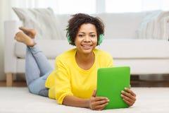 有片剂个人计算机和耳机的愉快的非洲妇女 免版税库存图片