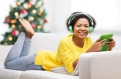 有片剂个人计算机和耳机的愉快的非洲妇女 库存图片