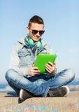 有片剂个人计算机和耳机的愉快的年轻人 免版税图库摄影