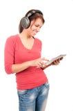 有片剂个人计算机和耳机的新学员女孩 免版税库存图片