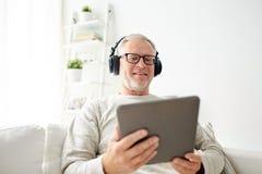 有片剂个人计算机和耳机的老人在家 免版税库存图片