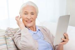 有片剂个人计算机和耳机的资深妇女在家 免版税库存图片