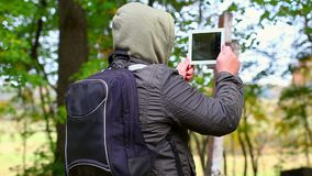 有片剂个人计算机和背包的远足者 股票录像