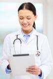 有片剂个人计算机和sthethoscope的年轻医生 免版税库存图片