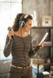 有片剂个人计算机唱歌卡拉OK演唱的少妇 免版税库存图片