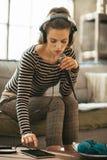 有片剂个人计算机唱歌卡拉OK演唱的少妇 免版税图库摄影