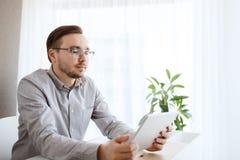 有片剂个人计算机在家办公室的创造性的男性工作者 免版税库存图片