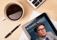 有片剂个人计算机显示杂志封面的和一杯咖啡的工作场所在一个木工作表上的 免版税库存照片