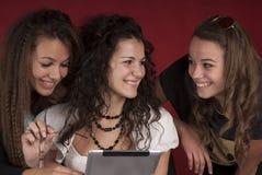 有片剂个人计算机的三个女孩 库存照片