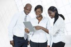 有片剂个人计算机的三个非洲商人 免版税库存照片