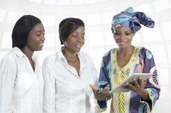 有片剂个人计算机的三个非洲女商人 免版税库存照片