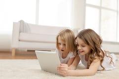 有片剂个人计算机的两个小女孩在家 图库摄影
