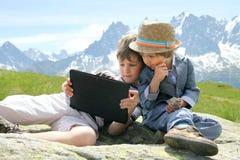 有片剂个人计算机的两个男孩在山 库存照片