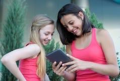 有片剂个人计算机的两个青少年的女孩 库存照片