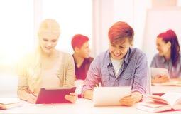 有片剂个人计算机的两名微笑的学生在学校 免版税图库摄影