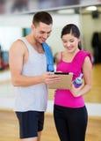 有片剂个人计算机的两微笑的人在健身房 免版税图库摄影