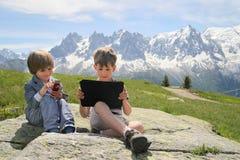 有片剂个人计算机的二个男孩在阿尔卑斯 库存图片