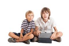 有片剂个人计算机的二个男孩,惊奇的面孔 库存照片