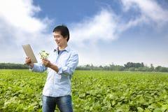 有片剂个人计算机的亚裔农夫 免版税库存图片