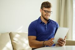 有片剂个人计算机的人在家 免版税库存图片