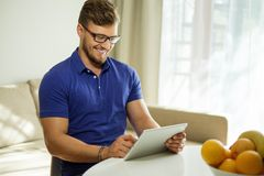 有片剂个人计算机的人在家 免版税图库摄影