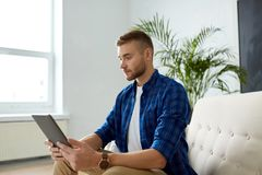 有片剂个人计算机的人坐沙发在办公室 免版税库存照片