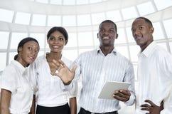 有片剂个人计算机的四个非洲商人 免版税库存照片