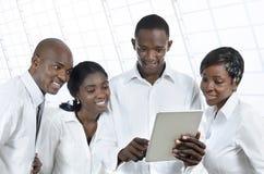 有片剂个人计算机的四个非洲商人 免版税图库摄影