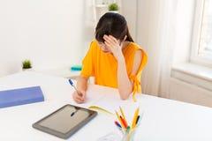 有片剂个人计算机的在家学会亚裔学生的女孩 免版税库存照片